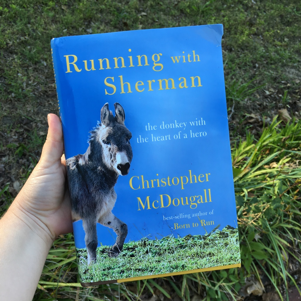 "Hand holding out the book ""Running with Sherman"" on a background with grass and a plant."