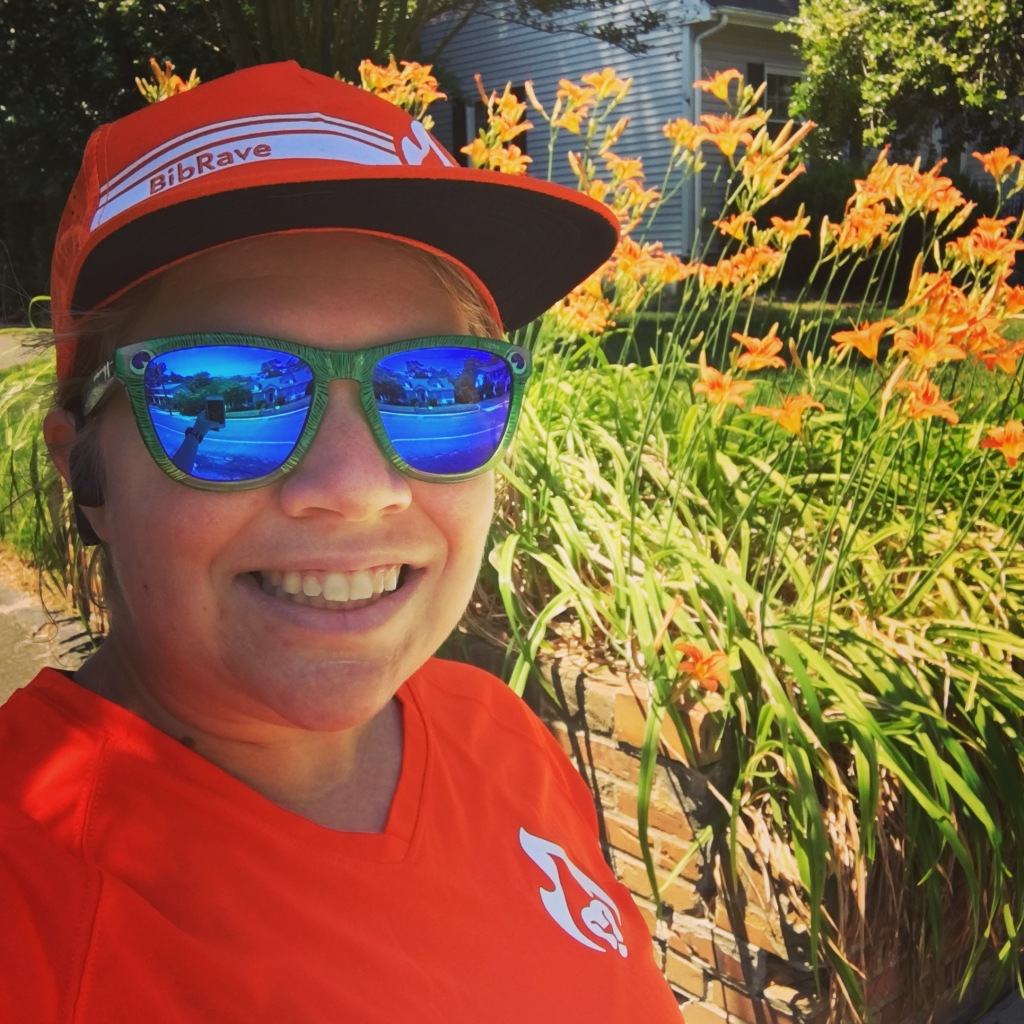 Vanessa Junkin, wearing an orange hat and shirt and green sunglasses with blue lenses, takes a selfie in front of orange flowers.