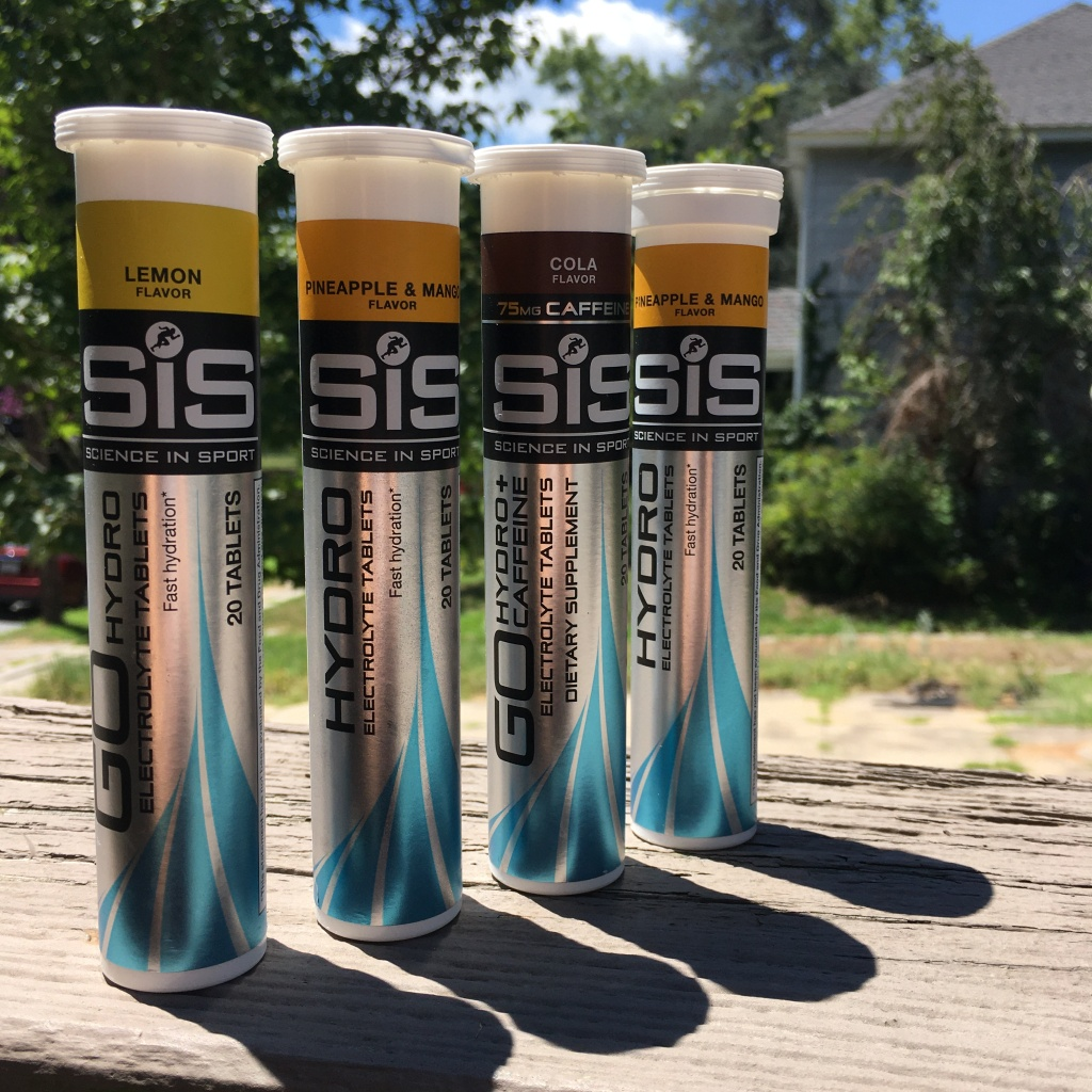 Four tubes of Science in Sport GO Hydro tablets outside, sitting on a deck railing. From front to back, Lemon, Pineapple & Mango, Cola, Pineapple & Mango.