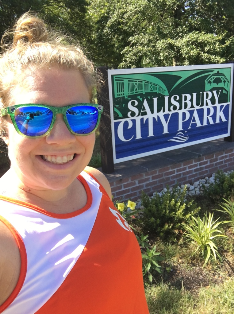 Vanessa Junkin taking a selfie in green and blue sunglasses and a white and orange tank top with a Salisbury City Park sign.