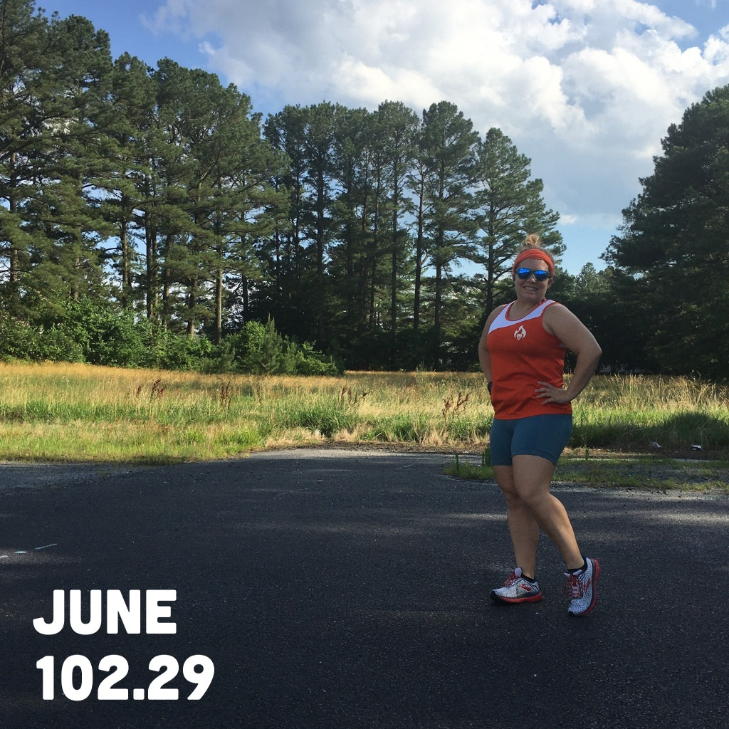 """Photo of Vanessa Junkin posing in orange and white tank top and blue shorts against a rural-looking backdrop with trees and clouds. The image includes the text """"June 102.29,"""" representing the amount of miles I ran."""