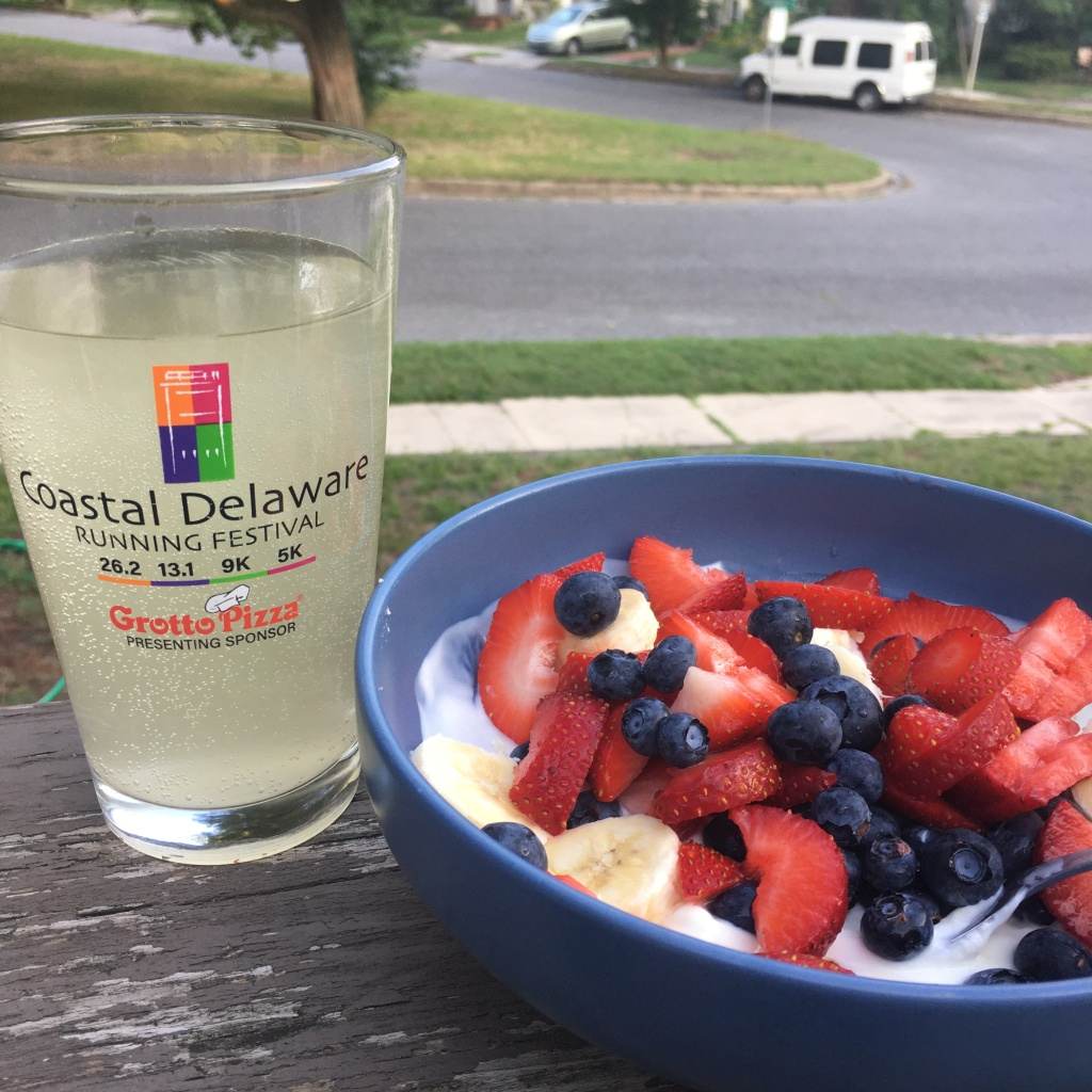Pint glass with very pale yellow drink (Science in Sport GO Hydro Pineapple & Mango) and a blue bowl with strawberries, blueberries, bananas and yogurt in it.