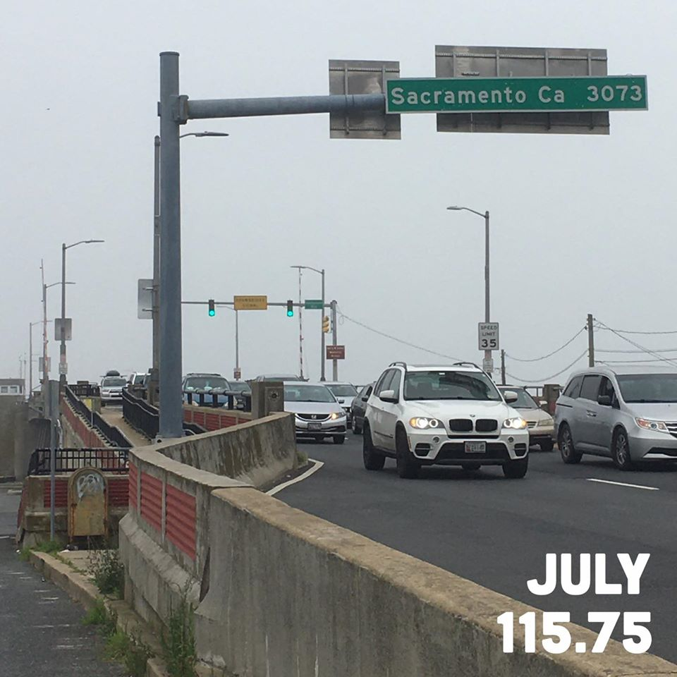 "Image showing the end of the bridge leading into Ocean City with a green road sign reading ""Sacramento Ca 3073."" Text at the bottom says ""July 115.75,"" for 115.75 miles run during July."