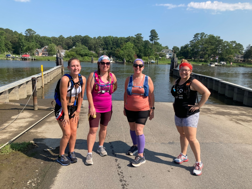 Four female runners pose for a photo in front of the Upper Ferry terminal (very small, just the road looking like it is turning into water).
