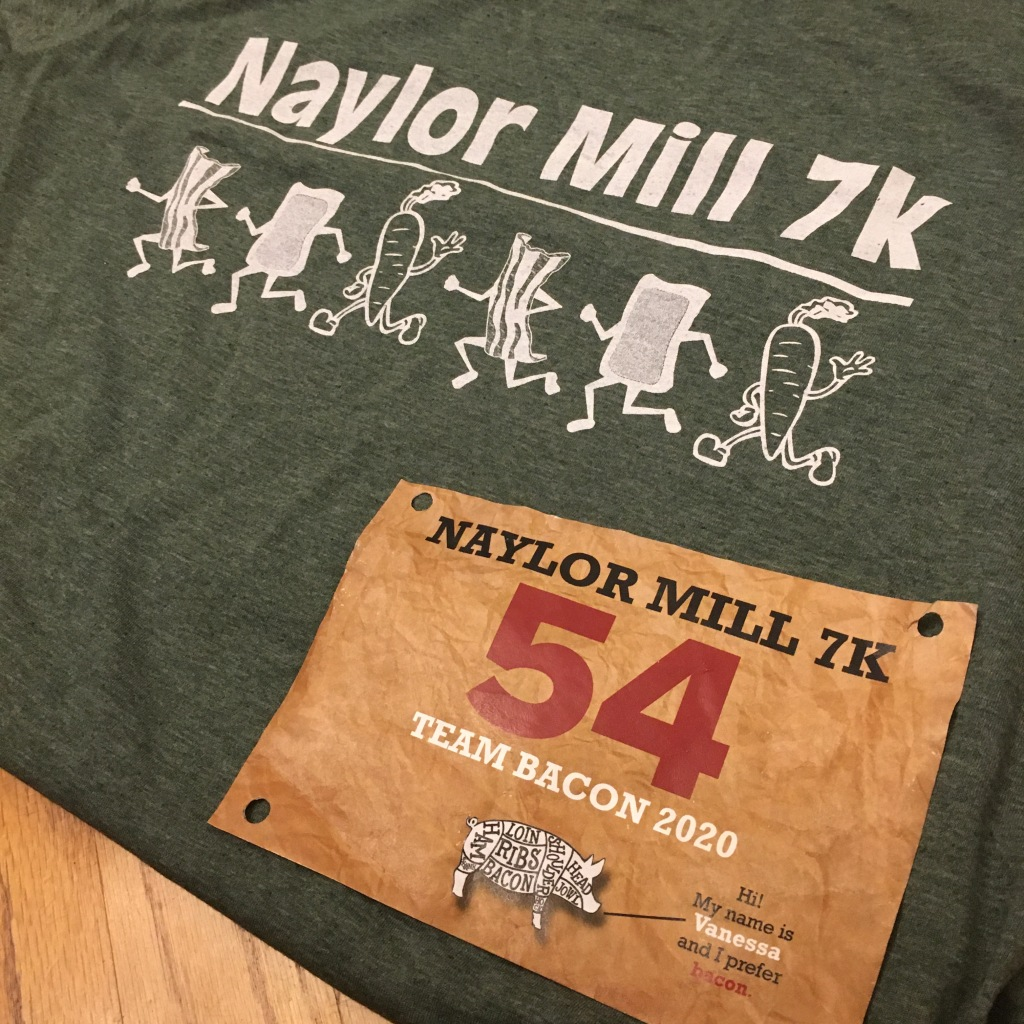 "Green T-shirt that says ""Naylor Mill 7K"" and has running bacon, scrapple and veggies on it, with the brown race bib on top."