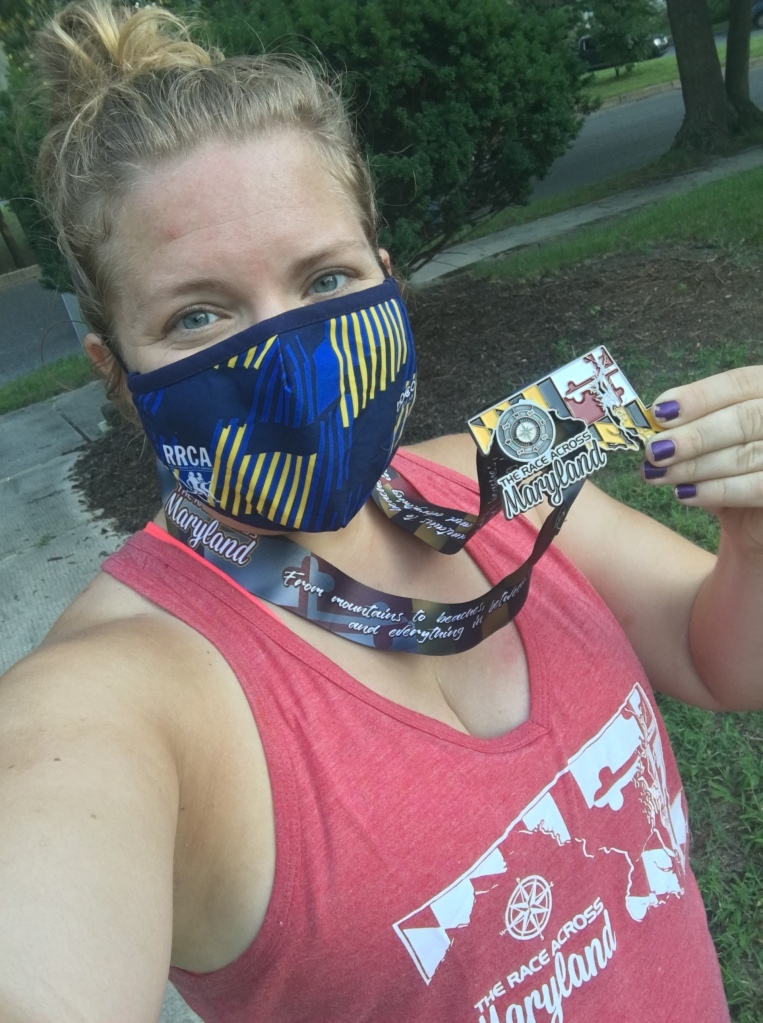 Selfie of Vanessa Junkin wearing mask and holding Race Across Maryland medal, wearing Race Across Maryland tank top.