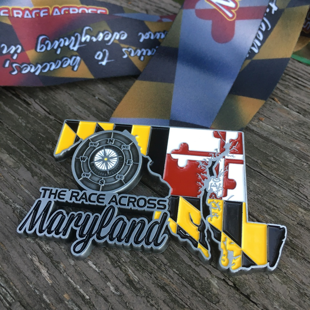 "Race Across Maryland medal, which is in the shape of Maryland with the Maryland flag design on it. It says ""The Race Across Maryland"" and has a compass."