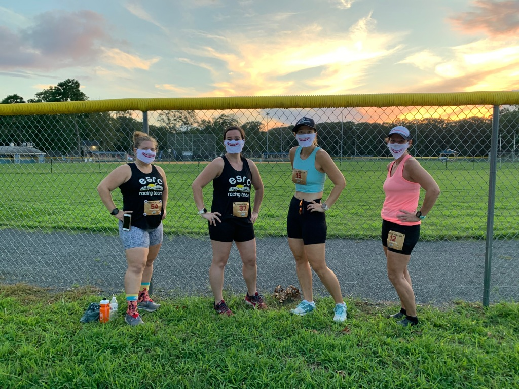Four female runners pose in front of a baseball field with a sunset behind them. All are wearing masks with a bacon image on it.