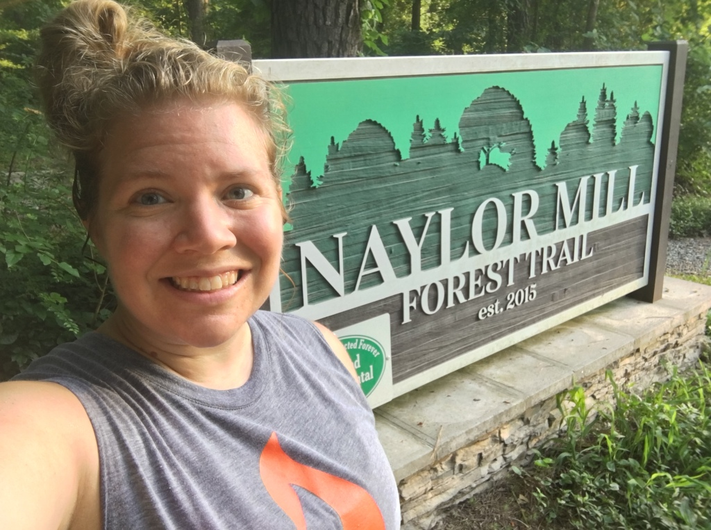 Vanessa Junkin poses in front of Naylor Mill Forest Trail sign.