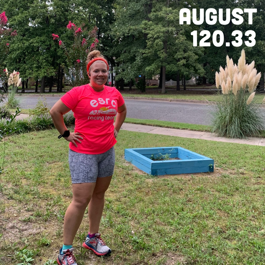 """Photo of Vanessa Junkin posing on some grass with trees behind her in bright pink shirt and gray-looking herringbone shorts. Text says """"August 120.33,"""" for 120.33 miles run in August."""