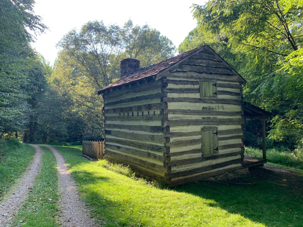 Historic cabin shown with trail on the left.