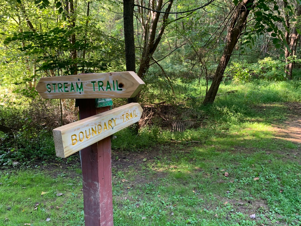 "Wooden markers, one reading ""Stream Trail"" and another reading ""Boundary Trail"" with woods in background."