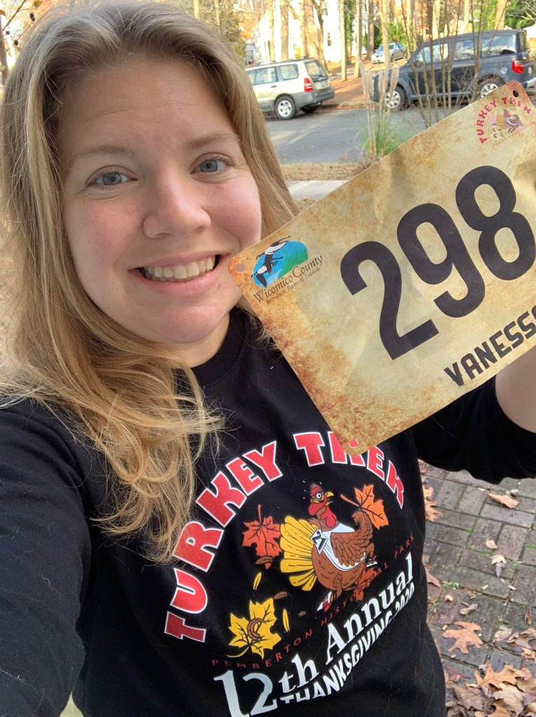 """Vanessa Junkin posing in black long-sleeved Turkey Trek shirt with personalized bib reading """"298"""" and """"Vanessa"""" (you can just see """"Vaness"""")."""