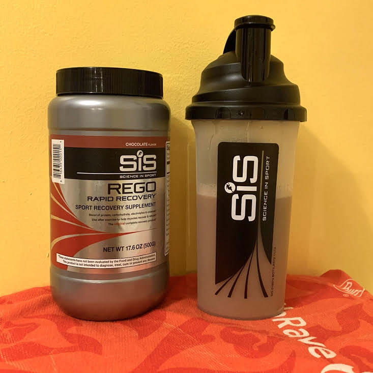 Canister of Science in Sport REGO Rapid Recovery next to a Science in Sport bottle showing the mixed chocolate drink.