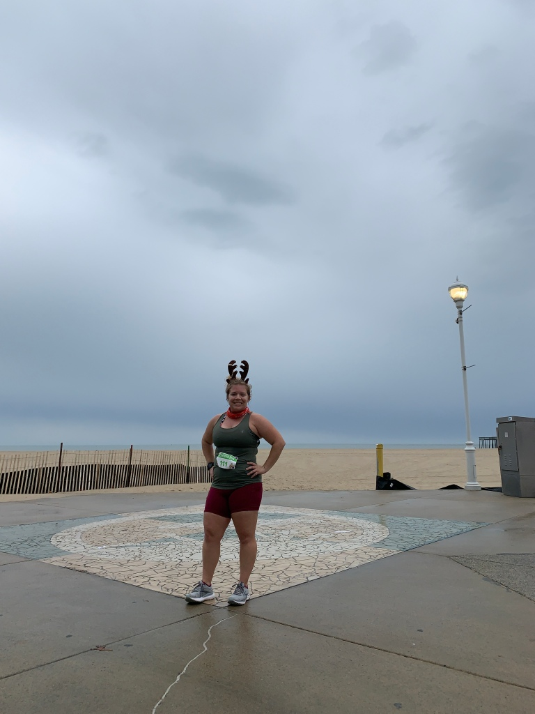 Female runner posing in front of beach wearing reindeer antlers, a green tank top, a race bib and maroon shorts.