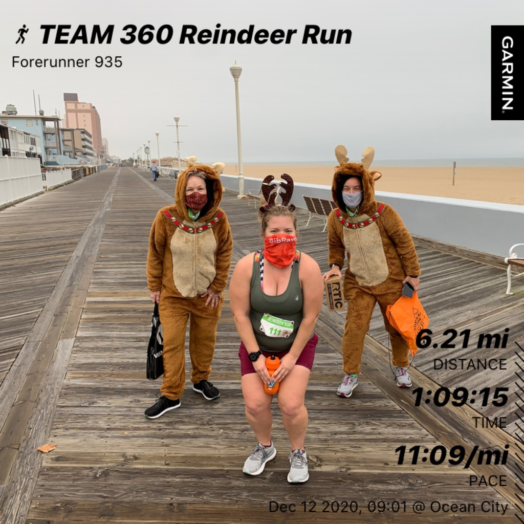 Female runner posing with dressed up reindeer on either side on the Ocean City Boardwalk.
