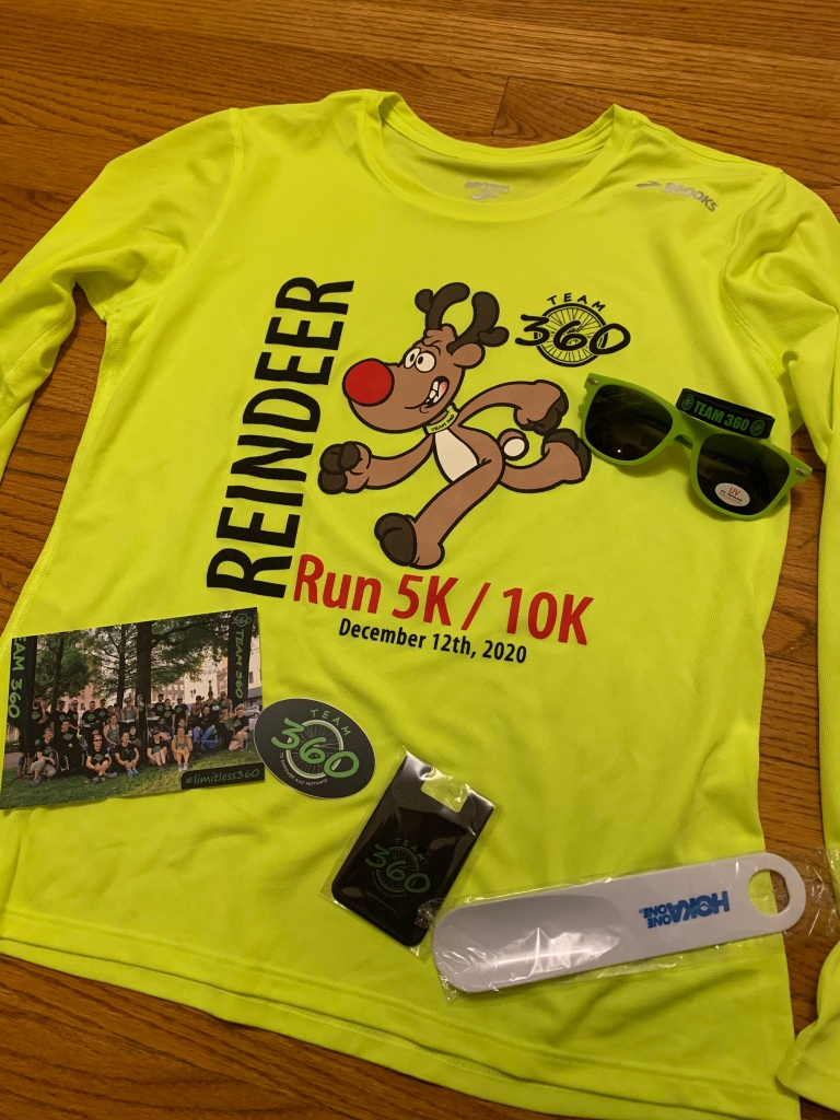 Reindeer Run long-sleeve tech shirt with various swag items around it (sunglasses, postcard, bracelet, sticker, etc.)