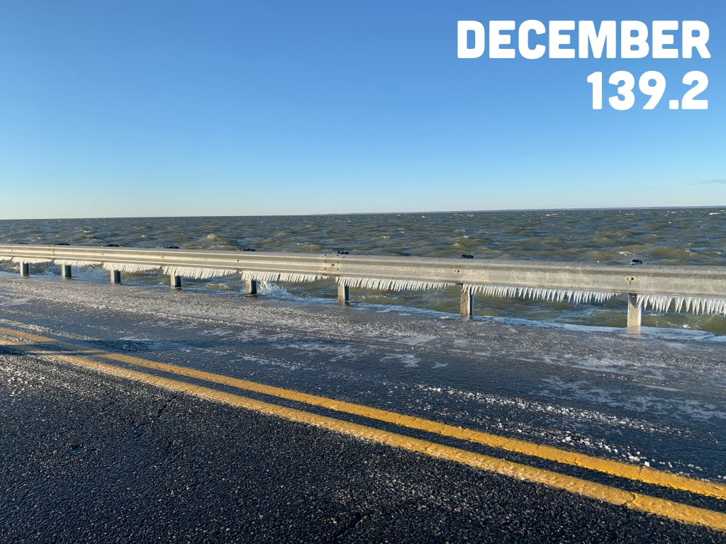 "Photo of an icy road alongside choppy water with icicles along a guardrail, with the text ""December 139.2"" on it."