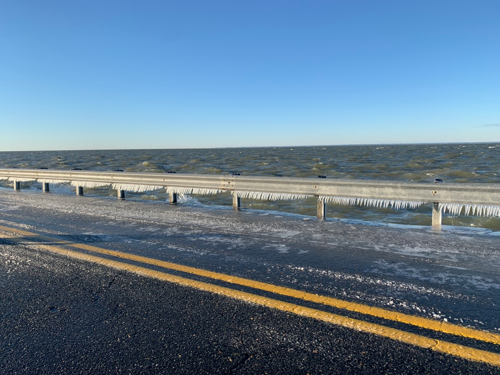 A road next to choppy water, with icicles formed on the guardrail.