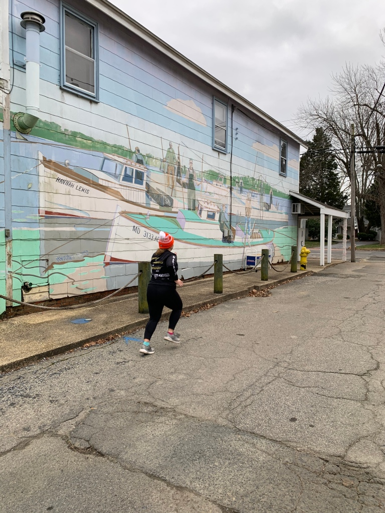 Female runner running away from camera with a mural on a building in the background.