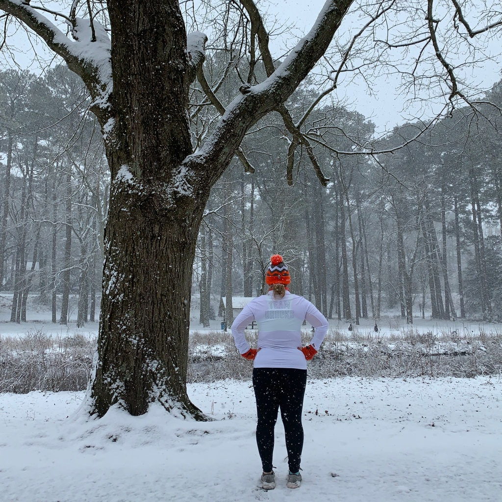 "Female runner wearing orange winter hat and gloves stands with her back to the camera. Back of shirt reads ""Team Brooks."" Photo is taken in the snow."