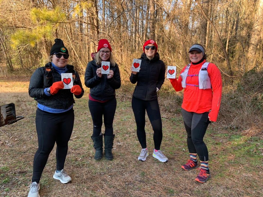 Four female runners in winter running gear holding handmade rectangular awards with a broken heart on them.