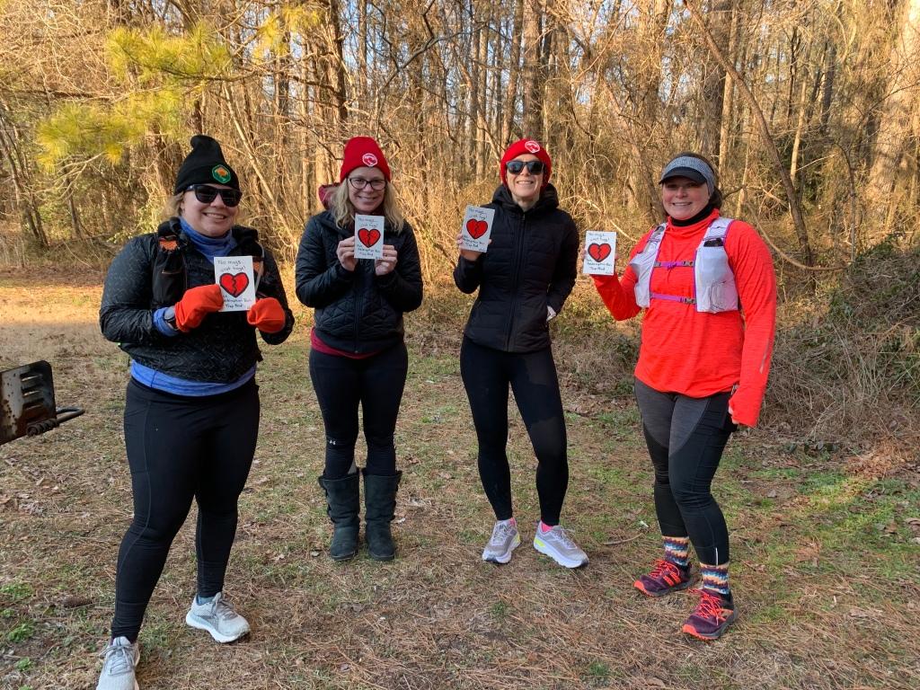 Four female runners in winter running gear holding handmade rectangular awards with a broken heart on them.