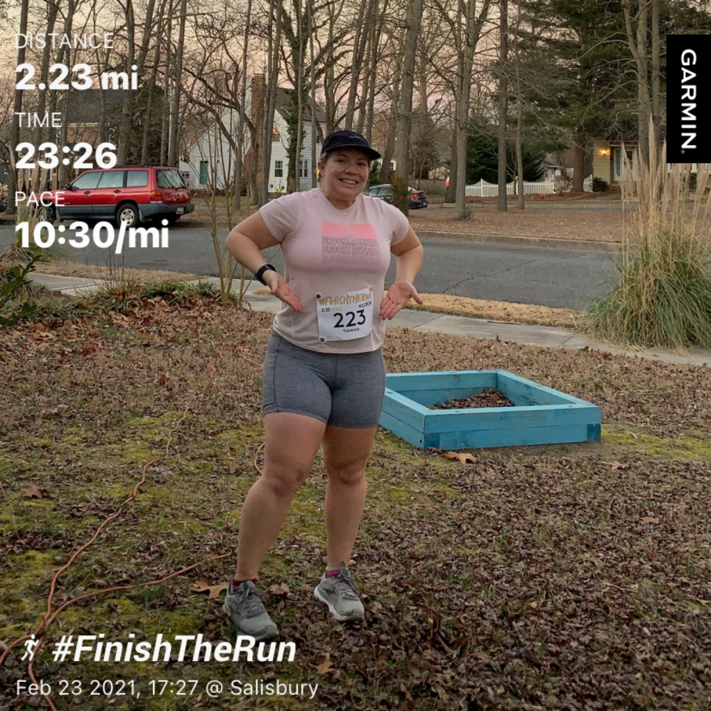 """Female runner posing with """"223"""" bib. Text reads """"Distance 2.23 mi, Time 23:26, Pace 10:30/mi"""" and at the bottom, """"#FinishTheRun, Feb 23 2021, 17:27 @ Salisbury."""""""
