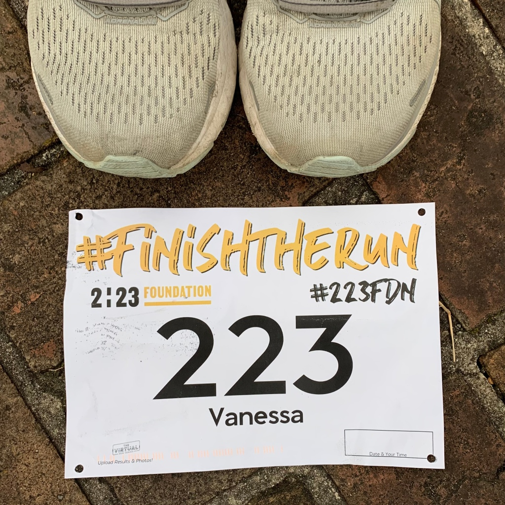 """The tops of running shoes above a race bib on the ground that reads #FinishTheRun, 2:23 Foundation and #223FDN, with the number """"223"""" and """"Vanessa"""" under that."""