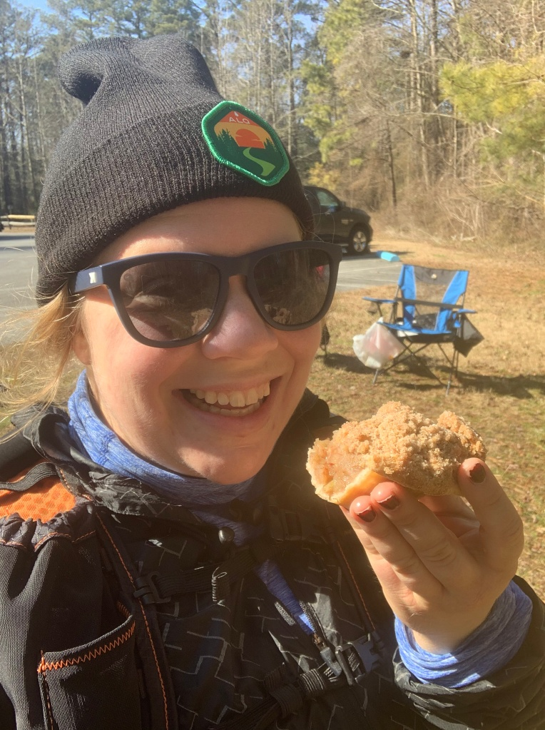 Selfie of female runner in hat and sunglasses with pie in her hand.