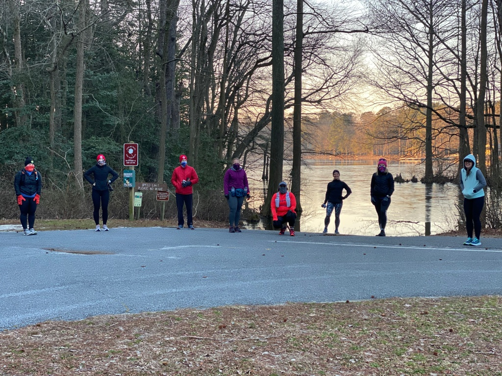 Spread-out runners in winter gear standing in a parking lot with a lake in the background.