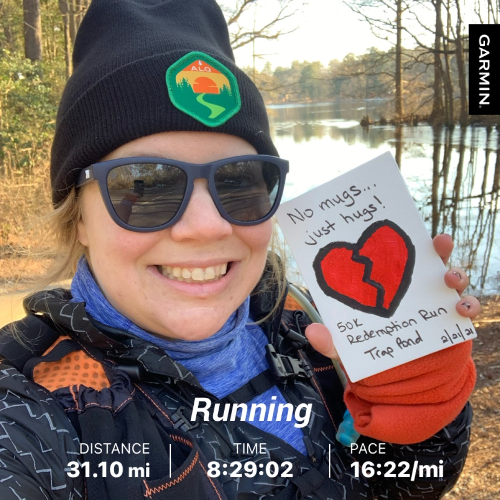 "Selfie of female runner in winter hat and sunglasses holding rectangular finisher award with broken heart on it. Text reads ""Running,"" ""Distance: 31.10 mi,"" ""Time 8:29:02,"" and ""Pace 16:22/mi."""