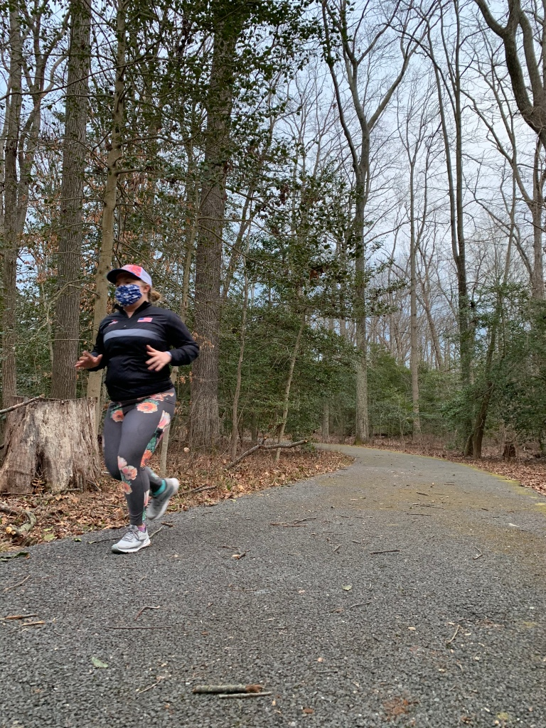 Female runner running on a paved trail, with woods in the background.