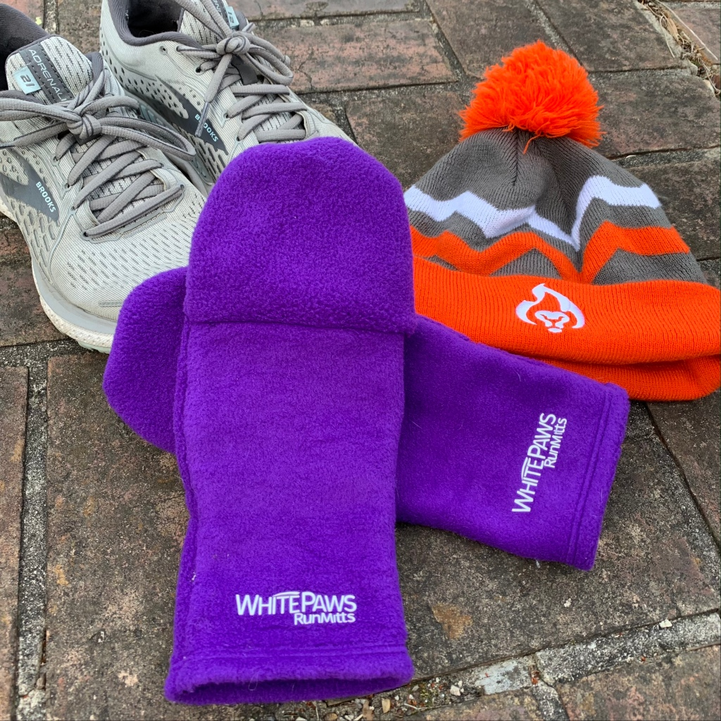 A pair of purple WhitePaws RunMitts are shown with a pair of Brooks Adrenaline running shoes to the left and an orange and gray BibRave winter hat to the right.