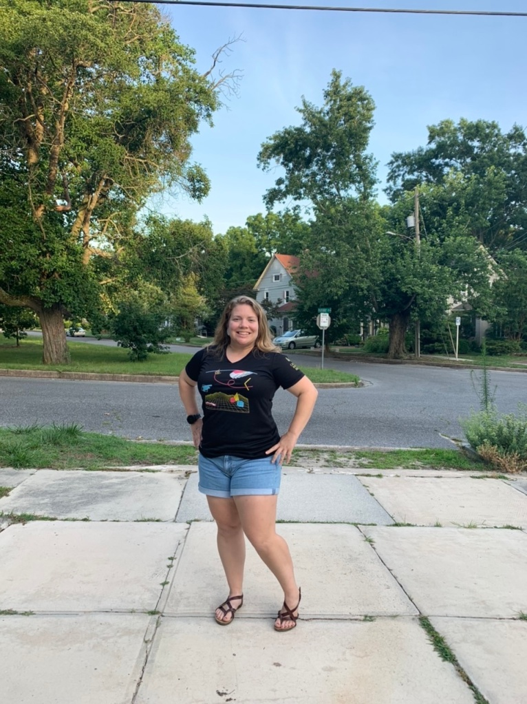 Vanessa Junkin poses outside in black race shirt with brightly-colored design and jean shorts.