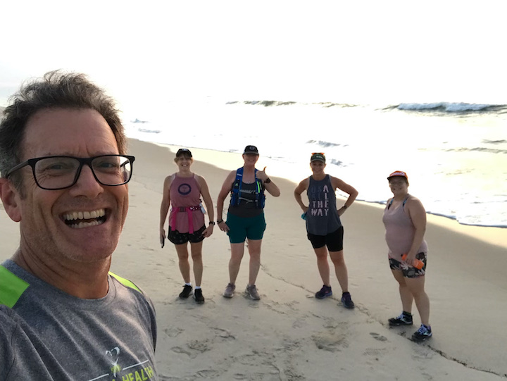 Group of runners in selfie on the beach.