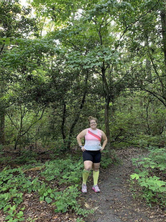 Vanessa Junkin posing in running clothes in the forest.