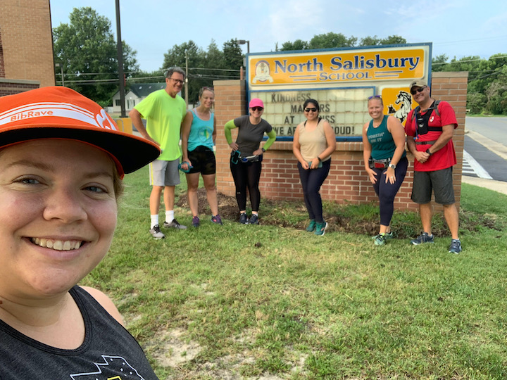 Group of runners posing by North Salisbury Elementary sign.