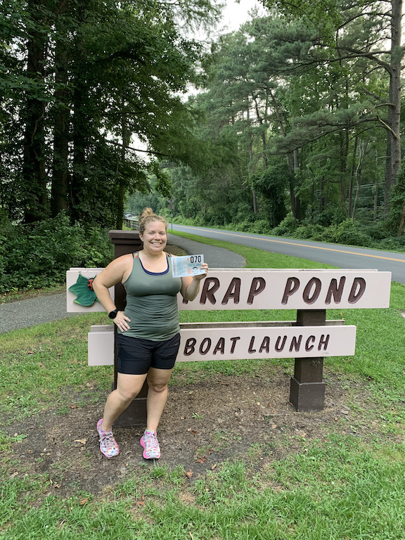 Vanessa Junkin posing with Tour de Salisbury bib in front of Trap Pond Boat Launch sign.