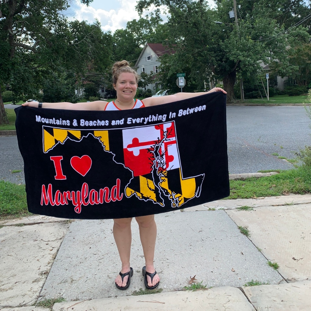 """Vanessa Junkin holds up black towel that has a shape of Maryland with the Maryland flag design. It says """"Mountains & Beaches and Everything in Between"""" at the top and """"I heart Maryland."""""""