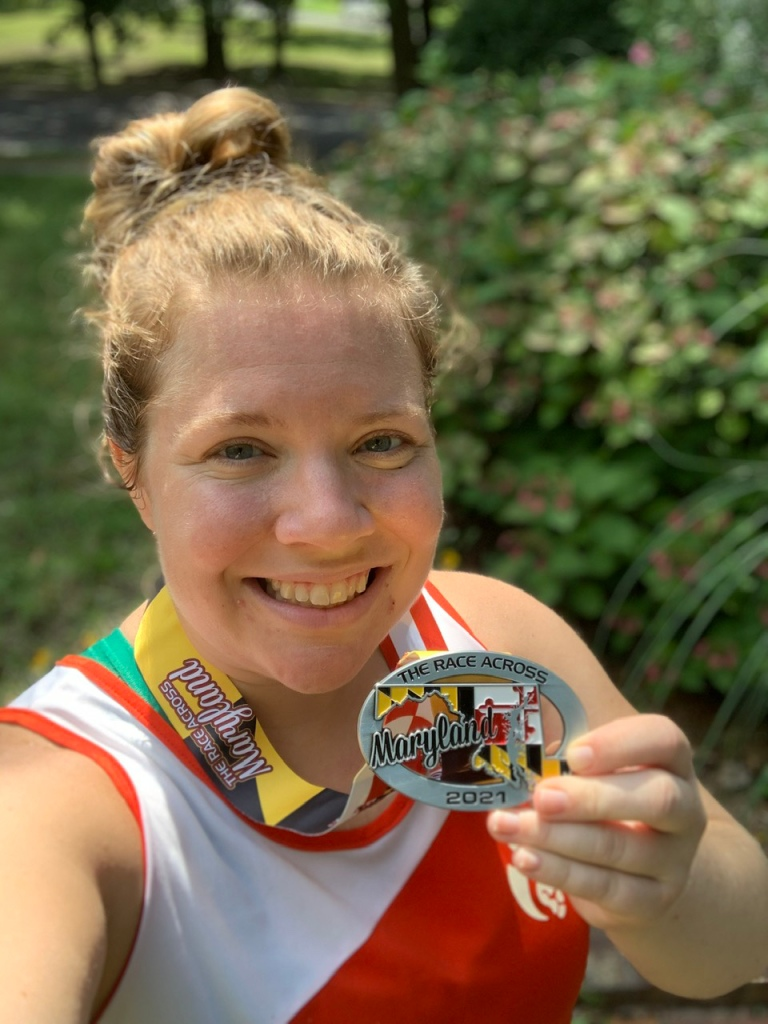 Vanessa Junkin takes a selfie with her Race Across Maryland medal.