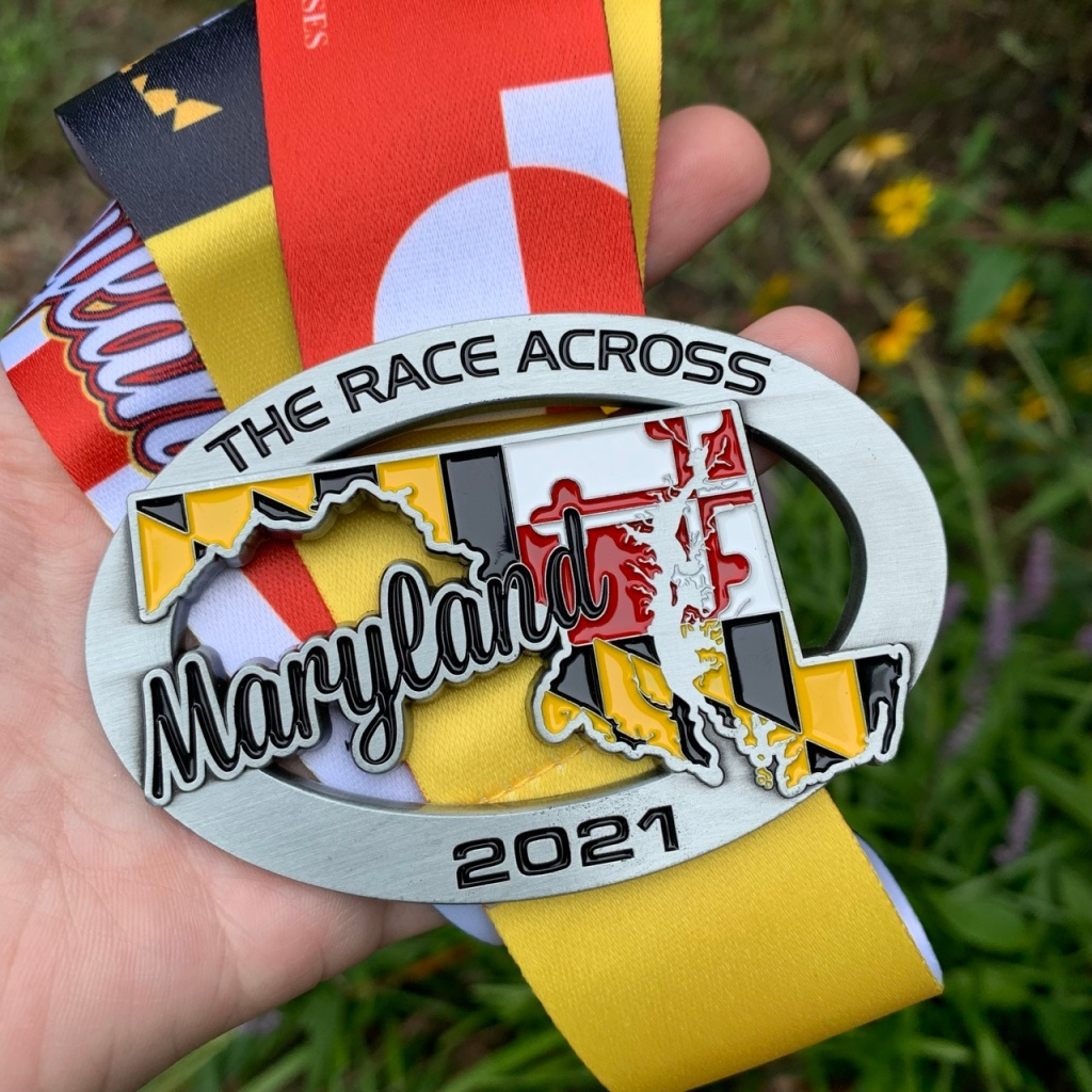 Close-up photo of Race Across Maryland medal, which has the state on it with the state flag pattern in the state.