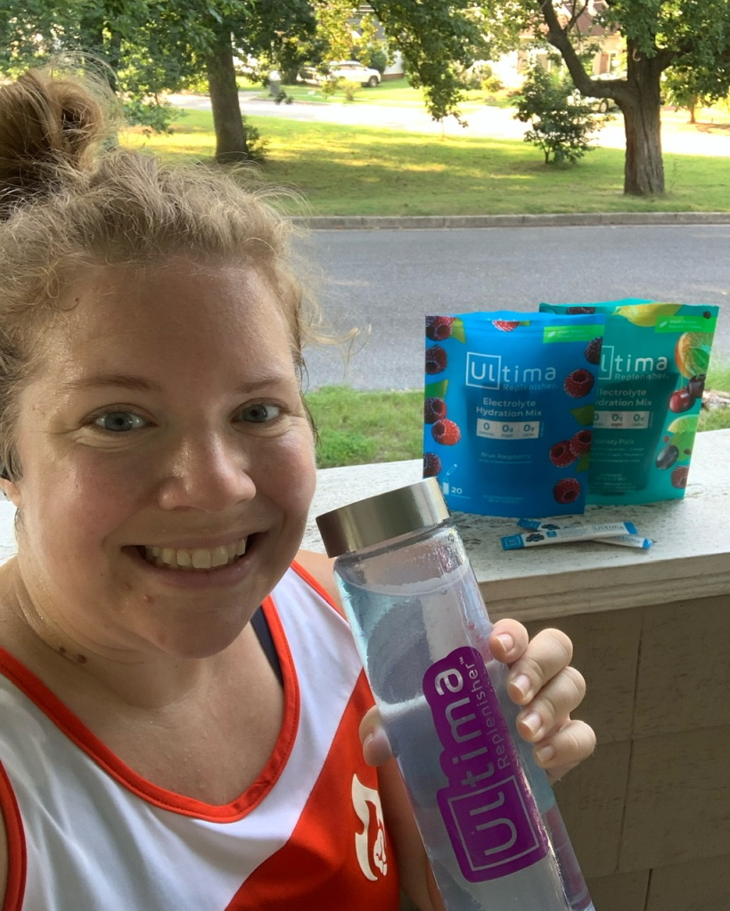 Vanessa Junkin posing with light blue drink in glass bottle and two pouches of Ultima Replenisher in the background.