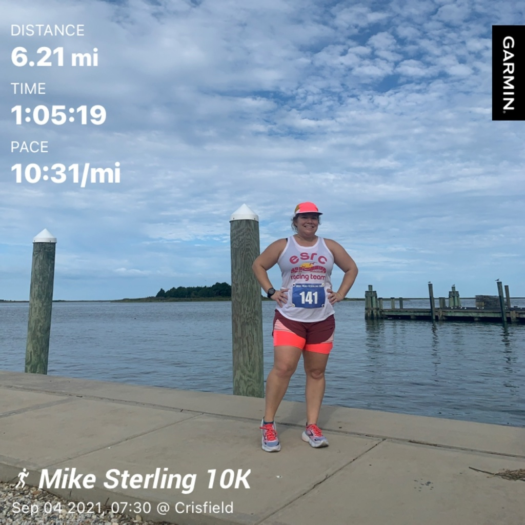 """Photo of Vanessa Junkin standing in running outfit in front of the water. Text says """"Distance 6.21 mi, Time 1:05:19, Pace 10:31/mi, Mike Sterling 10K, Sep 04 2021, 07:30 @ Crisfield."""""""