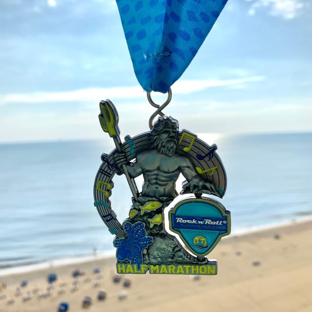 Rock 'n' Roll Virginia Beach Half Marathon finisher medal against backdrop of the beach.