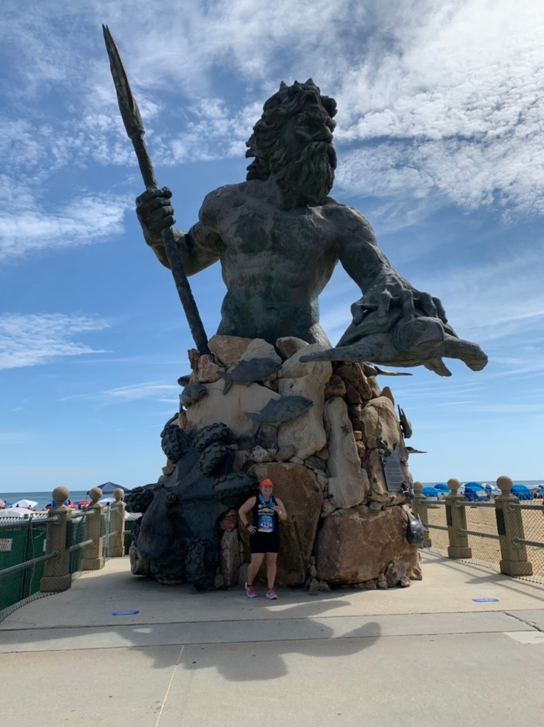 Vanessa Junkin posing for photo with large King Neptune statue in Virginia Beach.