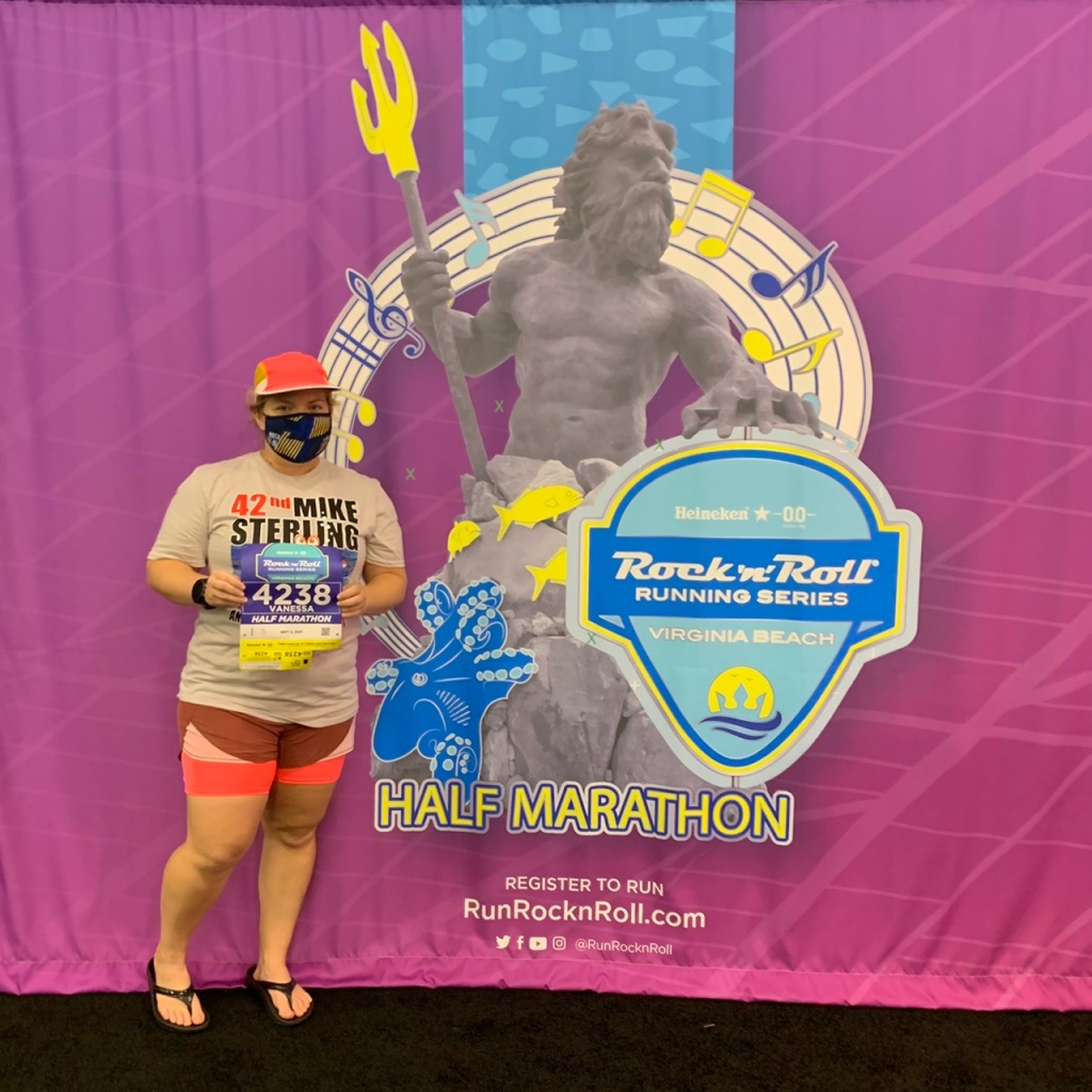 Vanessa Junkin posing with photo op showing King Neptune medal on a sheet behind her.