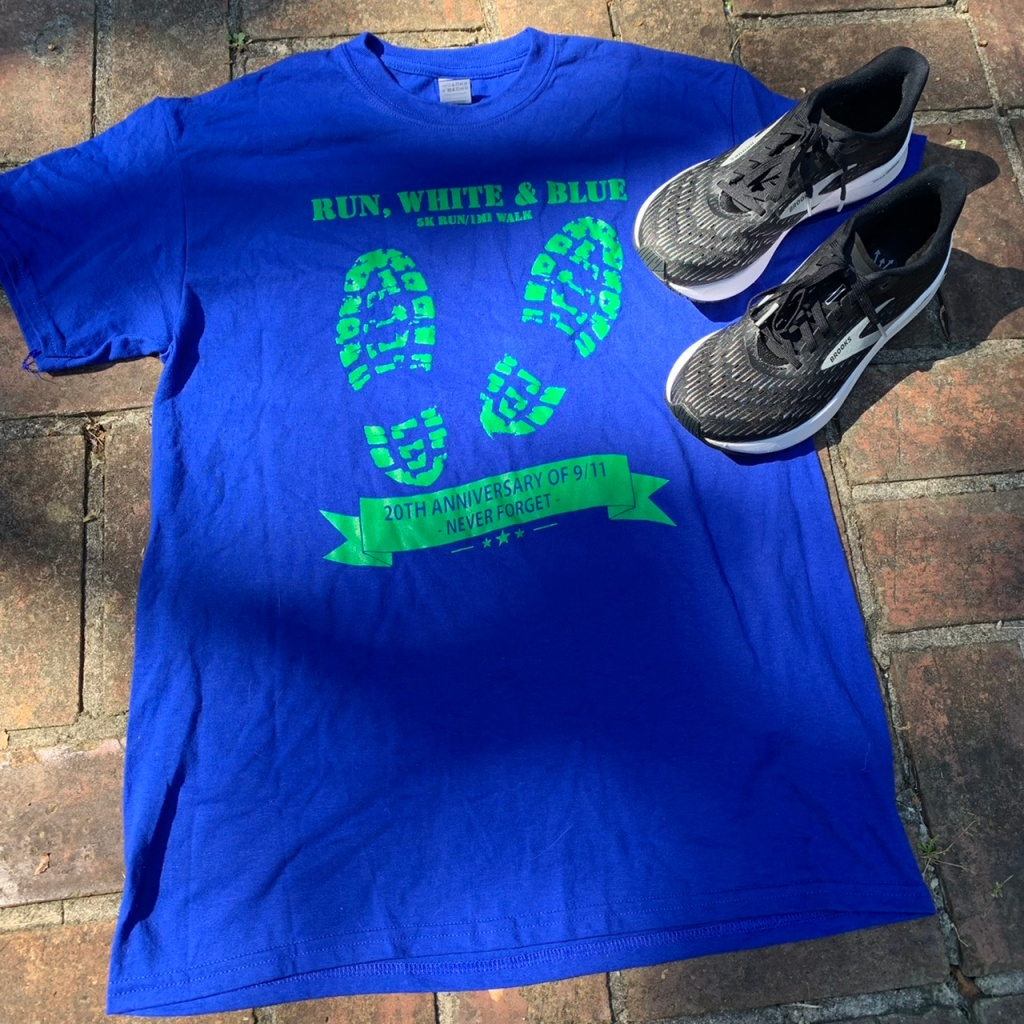 Blue T-shirt with green text along with black Hyperion Tempo running shoes on brick background.