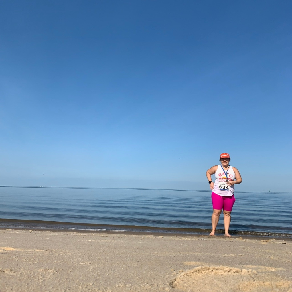 Vanessa Junkin standing at water's edge of small beach, wearing running clothes and holding medal.
