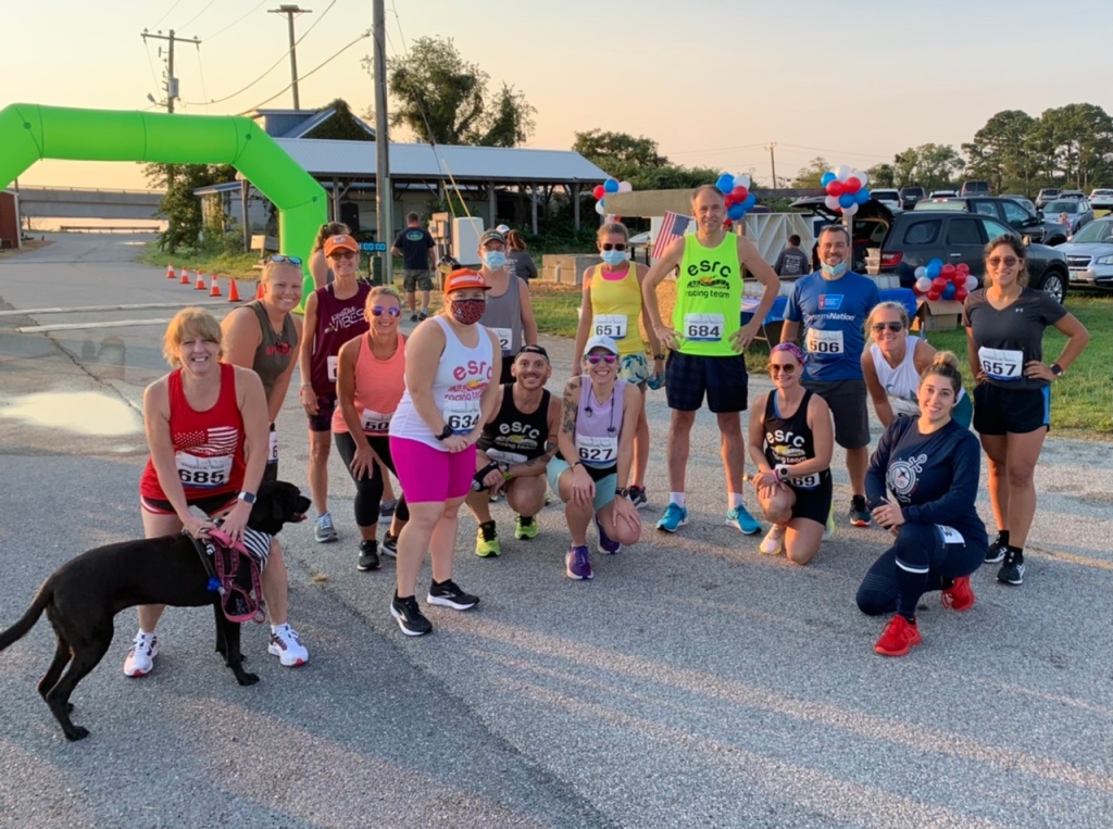 Group of runners poses for a photo near green race arch.